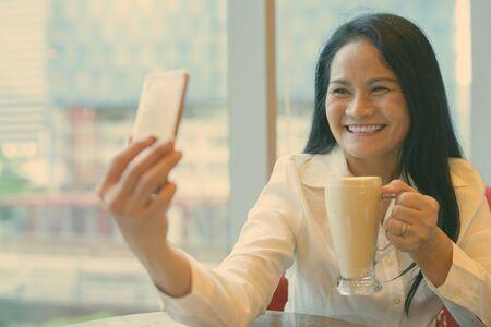 Mature beautiful Asian businesswoman relaxing inside the coffee shop