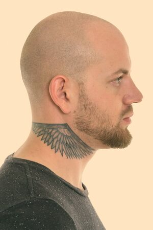 Profile view of face of young bald muscular man with tattoos