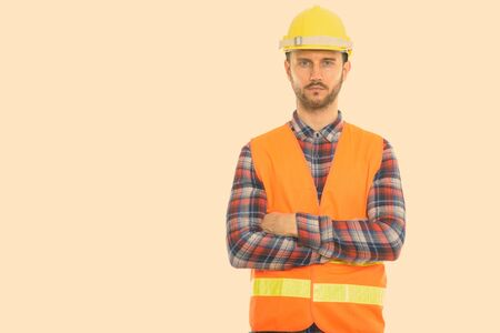 Foto de estudio de joven trabajador de la construcción con los brazos cruzados.
