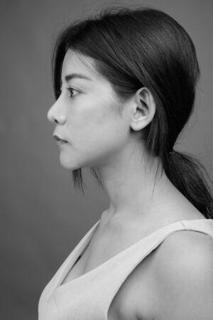 Junge schöne asiatische Frau gegen grauen Hintergrund