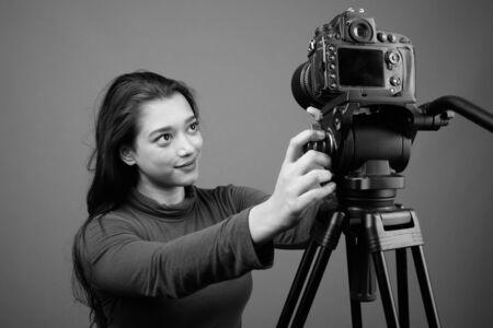 Jeune belle femme indienne vlogging sur fond gris Banque d'images