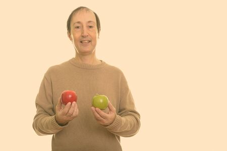 Studio shot of happy mature man smiling while holding red and green apple Stock Photo