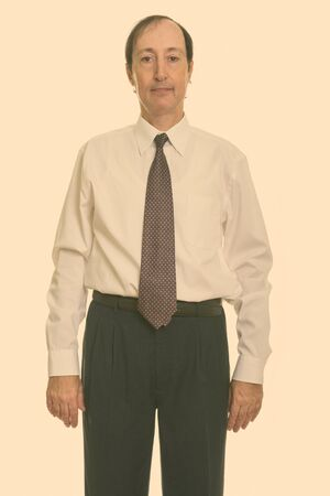Studio shot of mature businessman looking at camera
