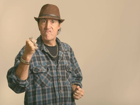 Studio shot of angry mature gangster man with fist raised