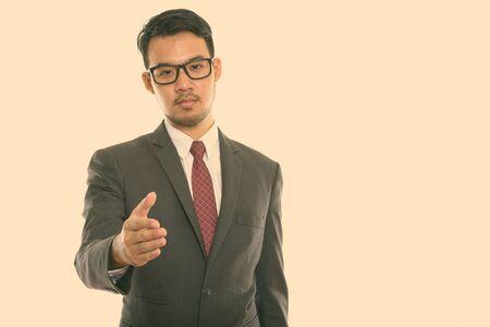 Studio shot of young Asian businessman giving handshake