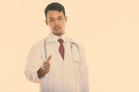 Studio shot of young Asian man doctor giving handshake