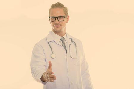 Studio shot of young handsome man doctor giving handshake