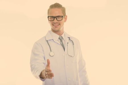 Studio shot of young happy man doctor smiling while giving handshake