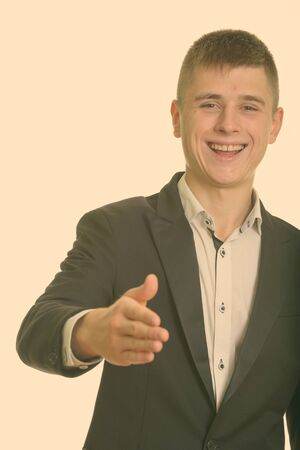 Studio shot of young happy businessman smiling and giving handshake Stok Fotoğraf