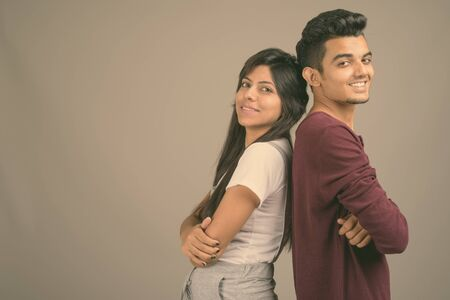 Young Indian man and young Indian woman together against gray background
