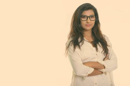 Studio shot of young beautiful Persian woman wearing eyeglasses with arms crossed isolated against white background