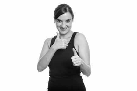 Studio shot of happy beautiful woman smiling and giving thumbs up