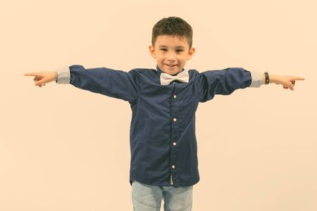 Studio shot of cute happy boy smiling and pointing fingers in different directions