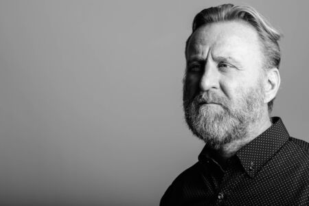 Studio shot of mature bearded man thinking while looking at distance in gray background