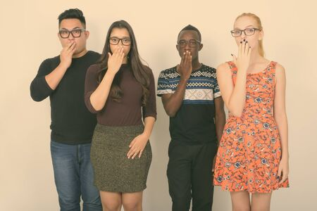 Studio shot of diverse group of multi ethnic friends looking shocked with eyeglasses together
