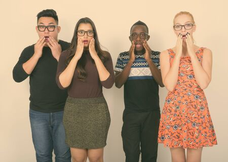Studio shot of diverse group of multi ethnic friends looking shocked while wearing eyeglasses together