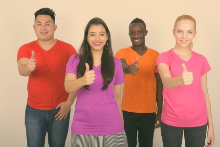 Studio shot of happy diverse group of multi ethnic friends smiling while giving thumb up together