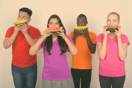 Studio shot of diverse group of multi ethnic friends thinking while covering face with slice of watermelon together
