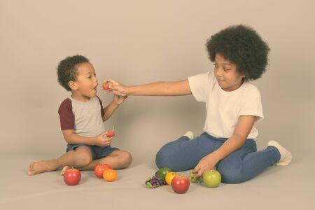 Junge niedliche afrikanische Geschwister zusammen gegen grauen Hintergrund