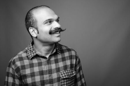 Indian man with mustache against gray background