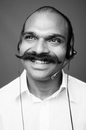 Uomo d'affari indiano come rappresentante del call center su sfondo grigio