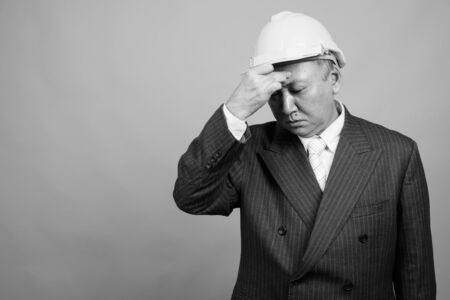 Mature Asian businessman as engineer with hardhat