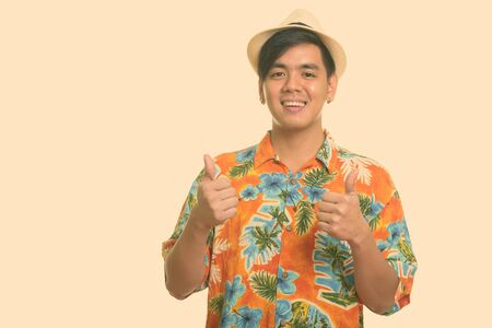 Young happy Asian man smiling and giving thumbs up
