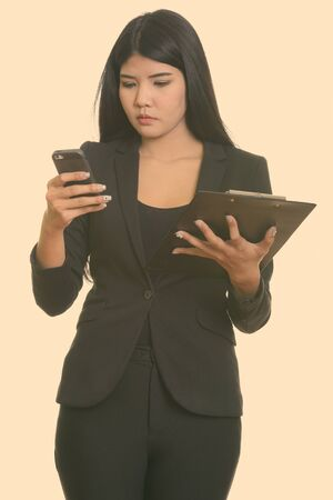 Studio shot of young Asian businesswoman using mobile phone while holding clipboard