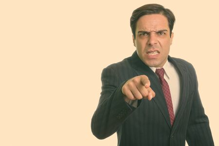 Studio shot of young Persian businessman looking angry while pointing at camera