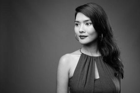 Studio shot of beautiful Asian businesswoman against gray background