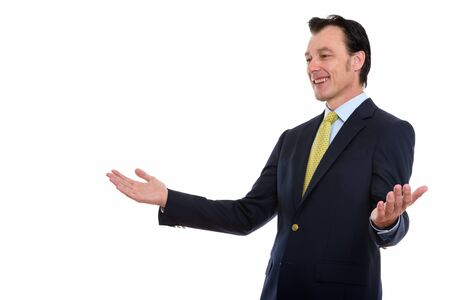 Studio shot of mature happy businessman smiling with arms raised