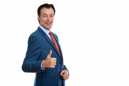 Studio shot of mature happy businessman giving thumbs up