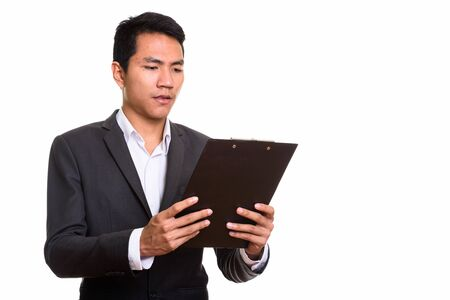 Studio shot of young Asian businessman reading on clipboard