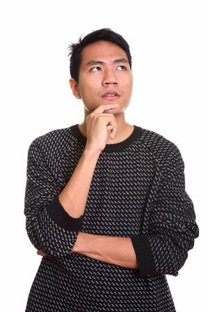 Studio shot of young Asian man thinking