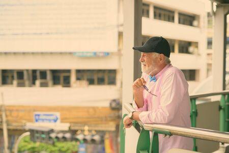 Handsome senior tourist man exploring the city