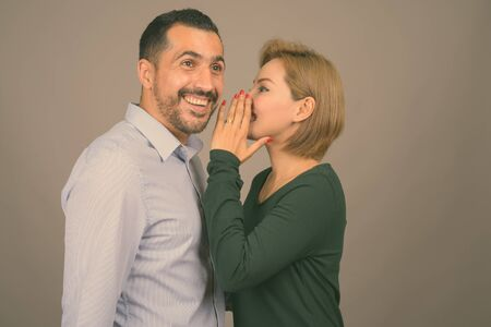 Multi ethnic couple together and in love against gray background Standard-Bild