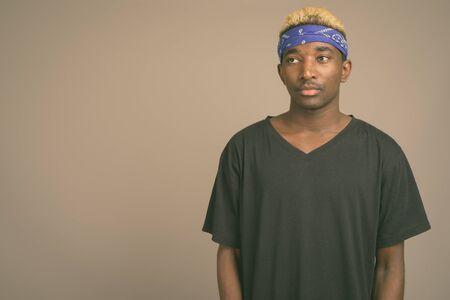 Young African man wearing blue bandanna as headband