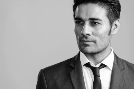 Face of young handsome Persian businessman in suit thinking