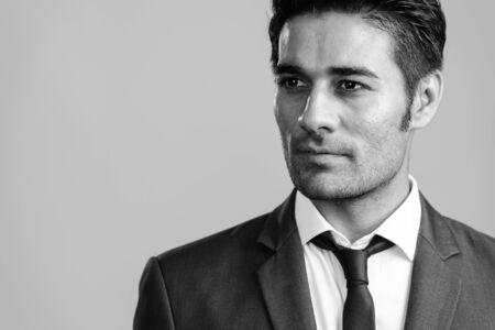 Gesicht des jungen gutaussehenden persischen Geschäftsmannes im Anzugdenken