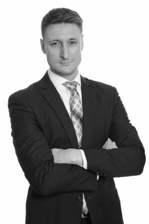 Retrato de joven empresario guapo en traje con los brazos cruzados.