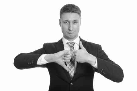Handsome Caucasian businessman giving thumbs up and down Stock Photo