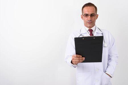 Portrait of mature handsome Persian man doctor Banco de Imagens