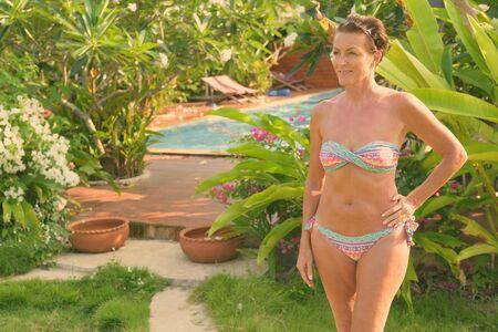 Mature beautiful tourist woman wearing bikini at the resort