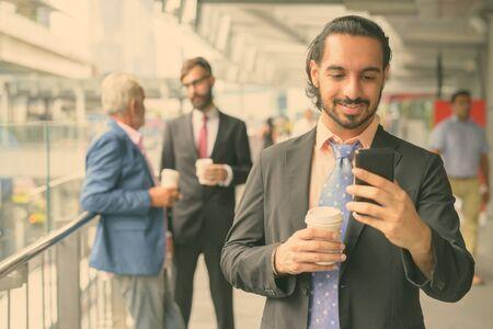 Three multi ethnic bearded businessmen together around the city