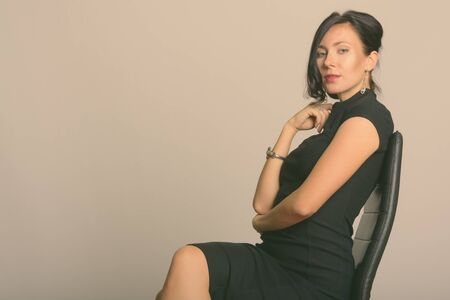 Studio shot of young beautiful businesswoman sitting on chair