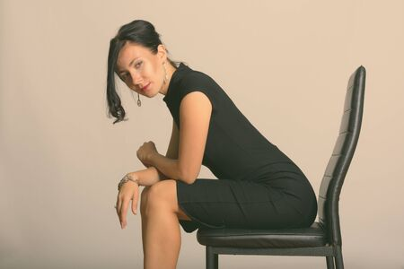 Studio shot of young beautiful businesswoman sitting on chair and bending back