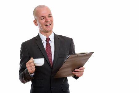 Studioaufnahme eines jungen glücklichen Geschäftsmannes mit Glatze, der lächelt und liest
