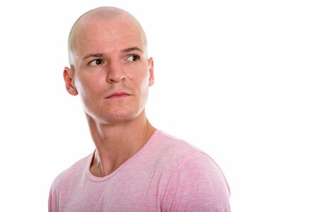 Studio shot of young handsome bald man thinking while looking ba