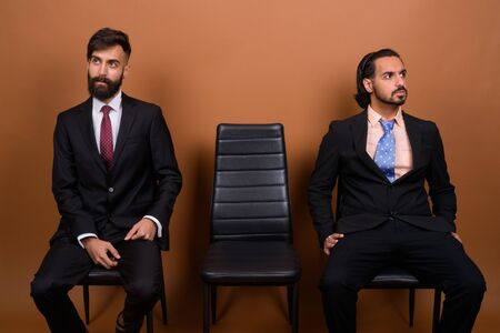 Two multi ethnic bearded businessmen together against brown background
