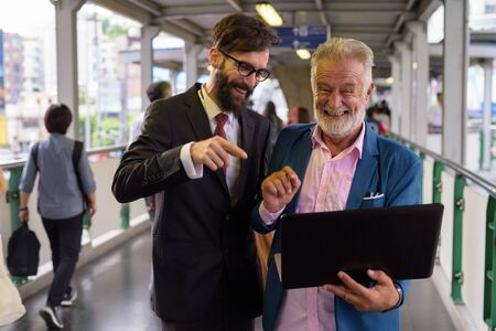 Two multi ethnic bearded businessmen together around the city Stock Photo